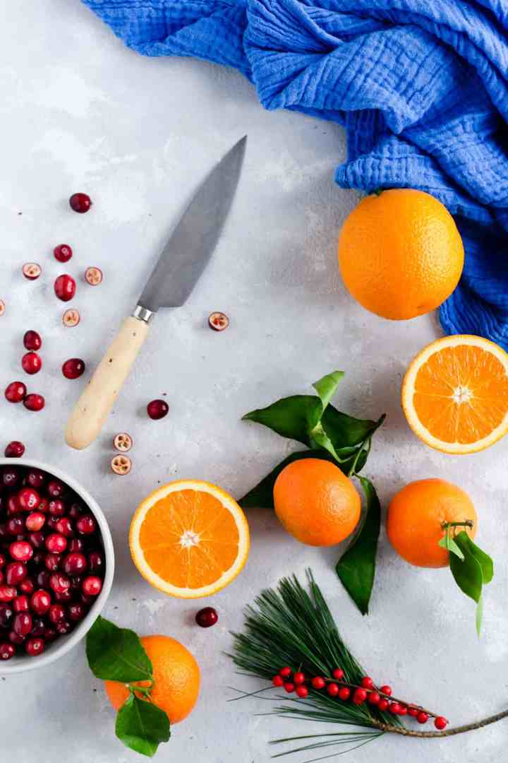 Overhead shot of some sliced oranges and clementines with a bowl of cranberries