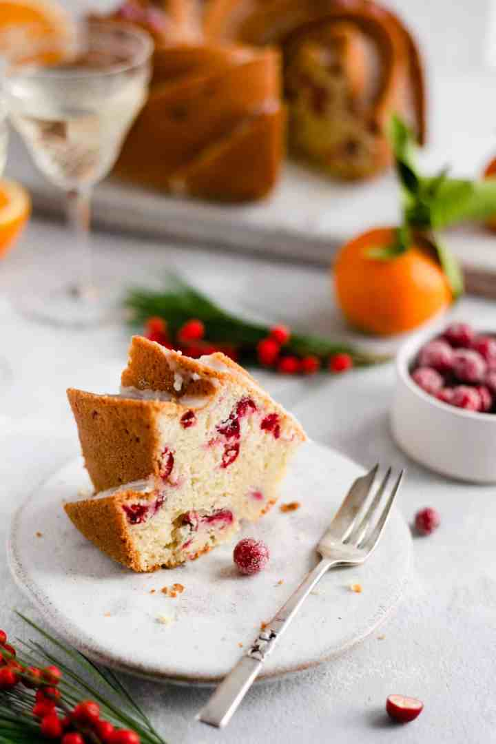 Slice of orange and cranberry cake on a plate with a small fork
