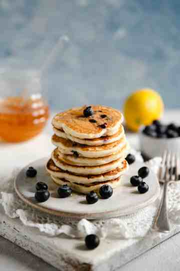 Straight ahead shot of blueberry pancakes on a small plate with honey jar at the back