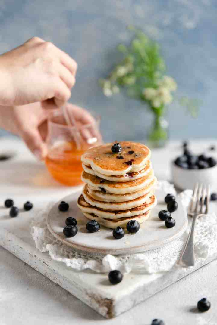 Straight ahead shot of small stack of blueberry pancakes with someone holding glass jar with agave nectar in the background
