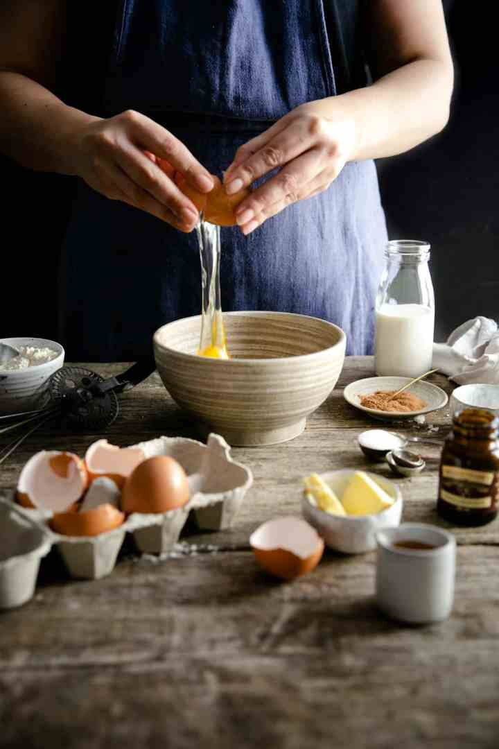 A person cracking an egg into a small bowl while preparing Dutch baby pancake