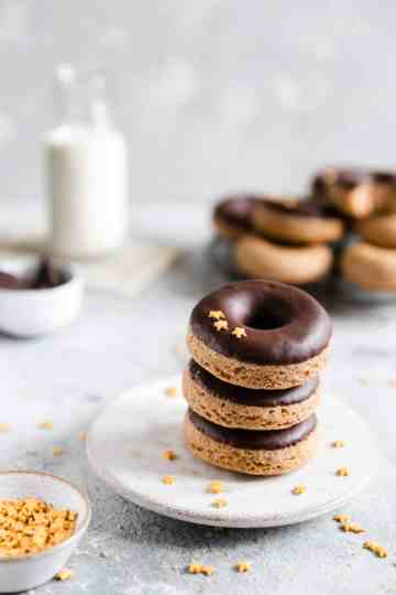 a stack of three baked doughnuts with chocolate glaze on a small plate