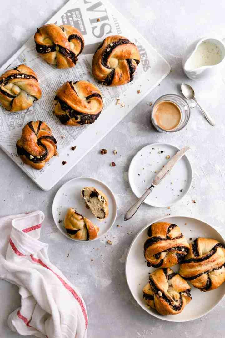 Overhead shot of chocolate hazelnut babka buns with small cup of coffee on side