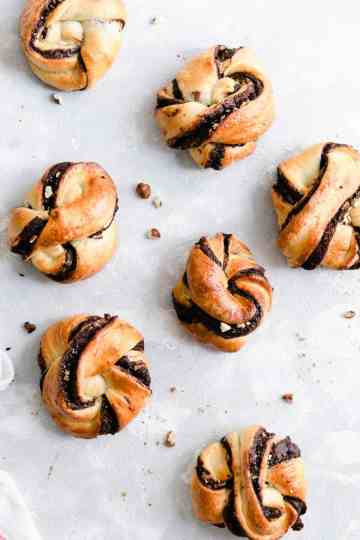 Overhead shot of baked chocolate hazelnut babka buns on a white background