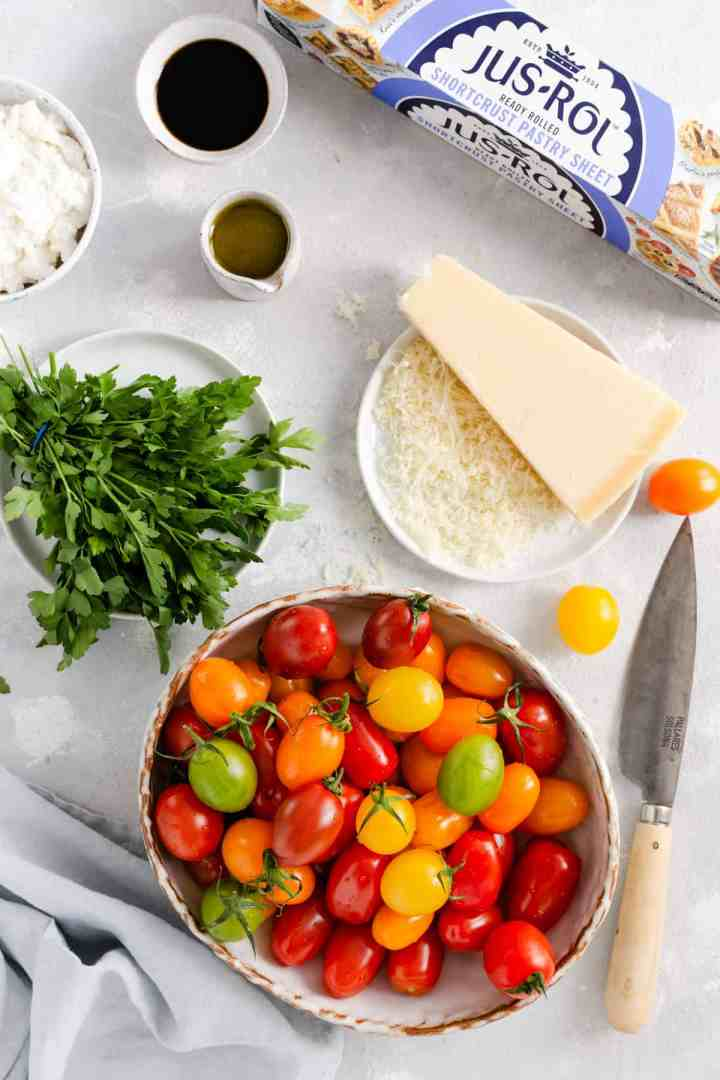 Overhead shot of the ingredients for mixed tomato and cheese tartlets: pastry, mixed baby plum tomatoes, ricotta, hard cheese, parsley, olive oil and balsamic glaze