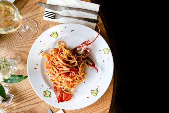overhead shot of white plate filled with lobster linguine