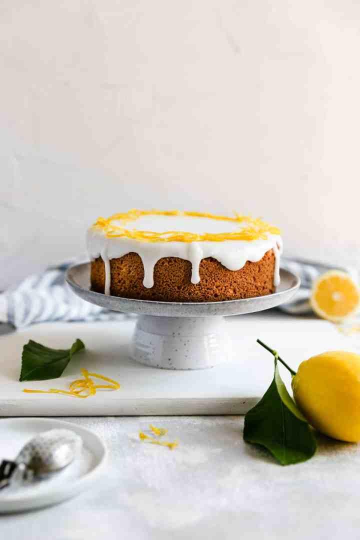 a straight ahead shot of a whole lemon cake on a cake stand