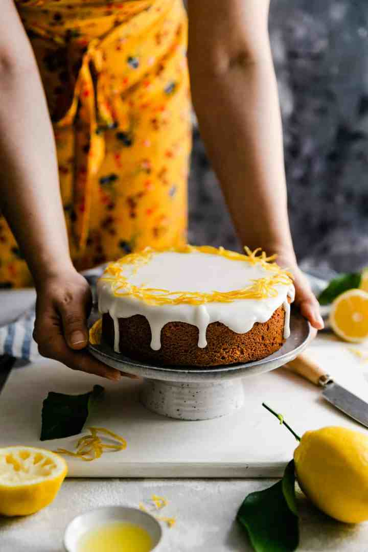 a side angle of a person holding a plate with whole lemon cake