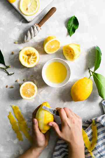 overhead shot of a person peeling a lemon with a small bowl of lemon juice and lemon halves on side