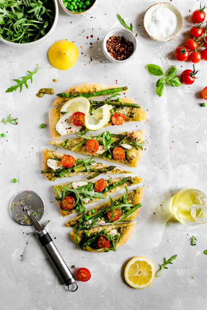 overhead shot of sliced rocket and asparagus pizza topped with cherry tomatoes