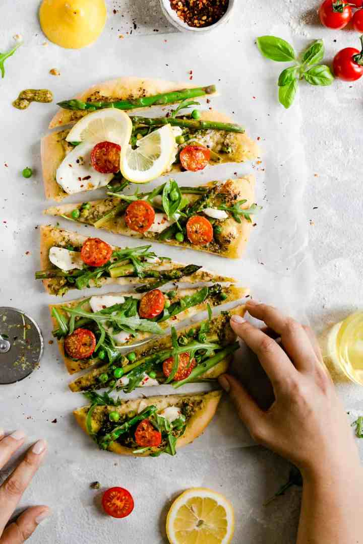 top view of someone reaching for a slice of homemade rocket and asparagus pizza