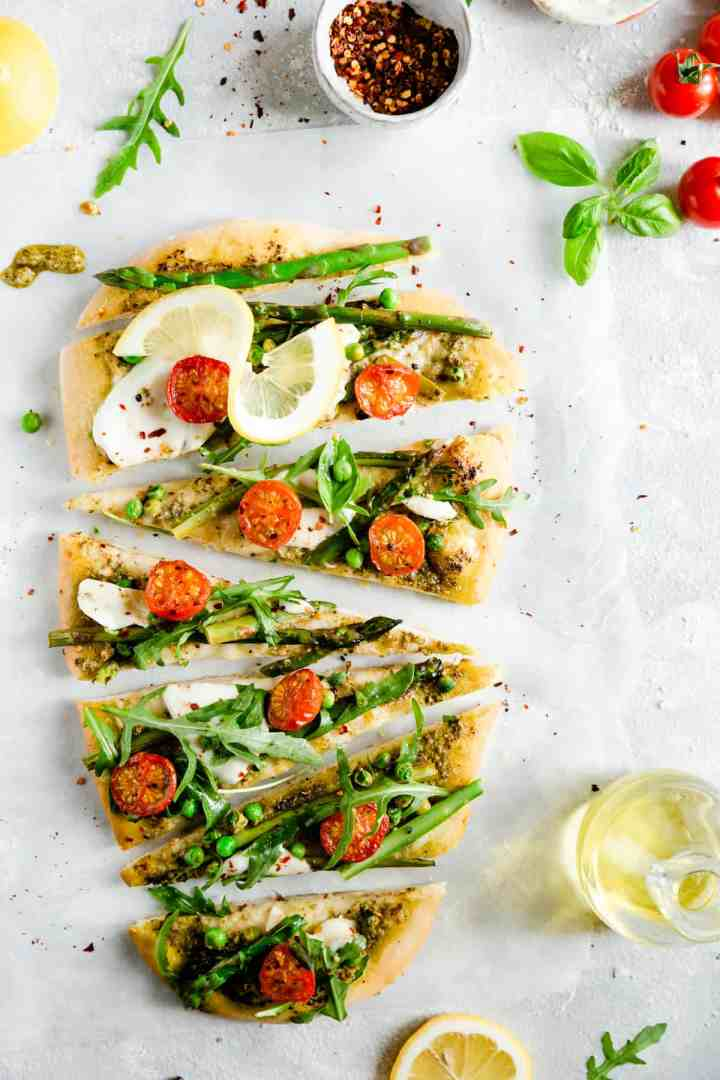 overhead shot of rocket and asparagus pizza cut into triangle slices