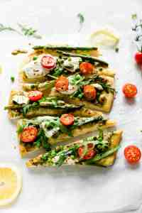 triangle slices of rocket and asparagus pizza topped with cherry tomatoes and mozzarella