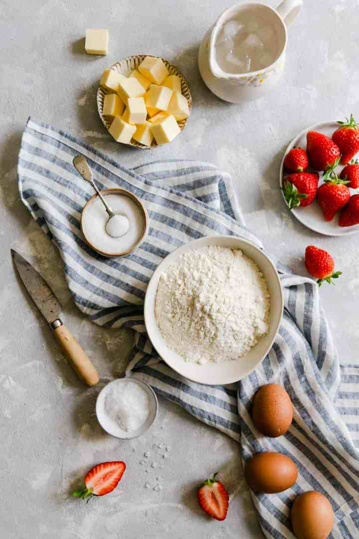 top view of ingredients for strawberry galette, flour, butter, sugar, salt, water and fresh strawberries