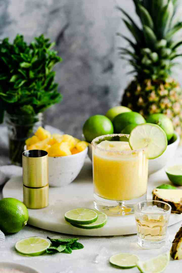 glass of frozen pineapple margarita on a marble chopping board
