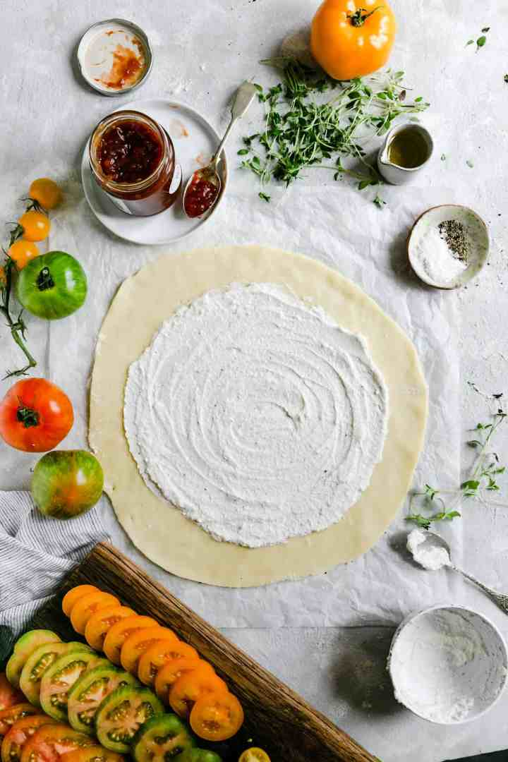 top view of a shortcrust pastry rolled into a circle and topped with ricotta cheese