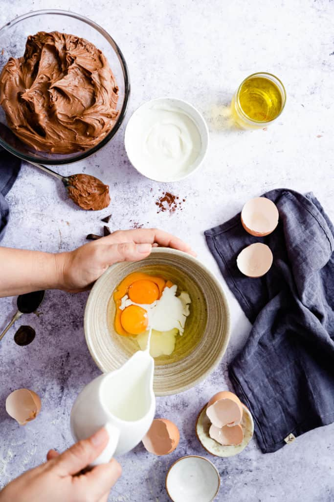 top view of a person pouring milk into a bowl with eggs