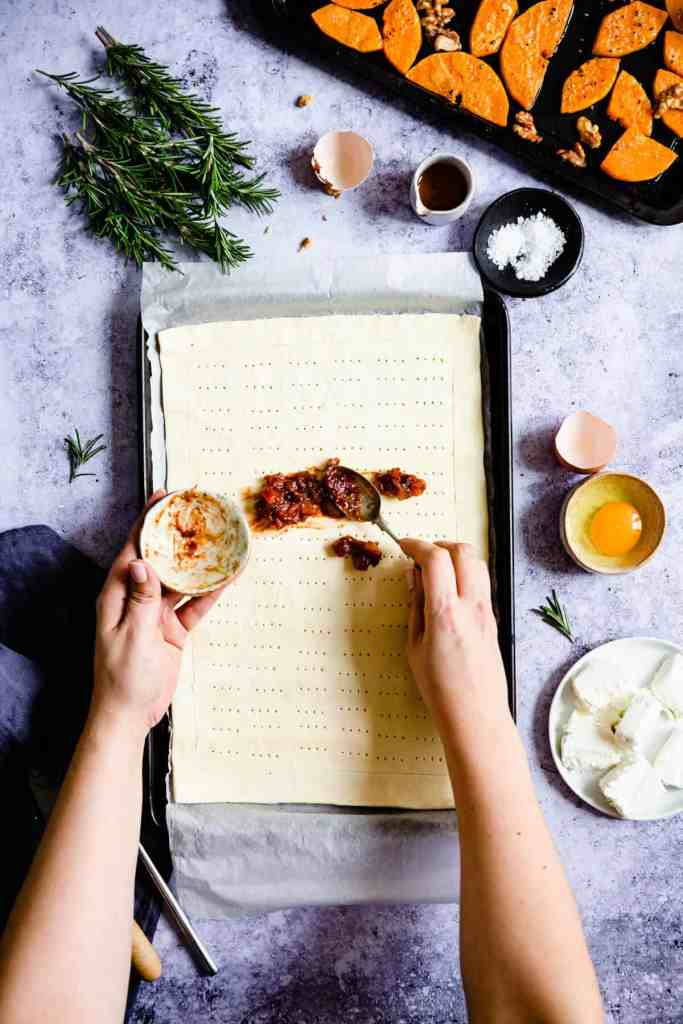 overhead shot of a person spreading chutney on puff pastry