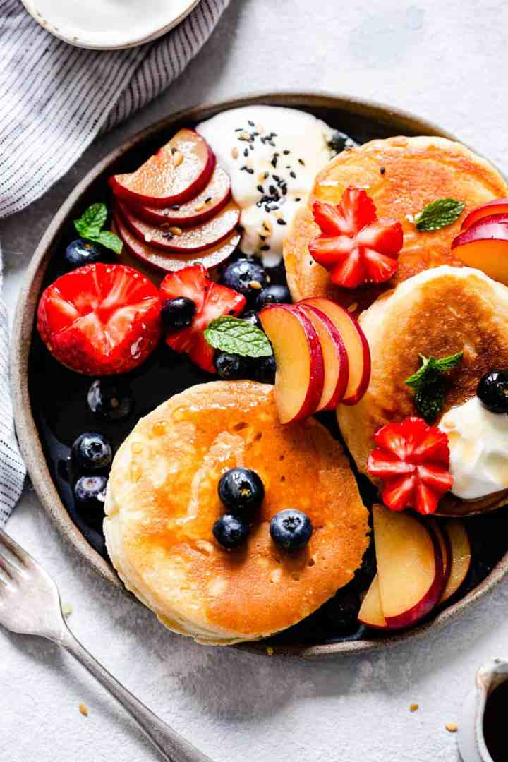 overhead shot of a plate with pancakes and selection of fruits