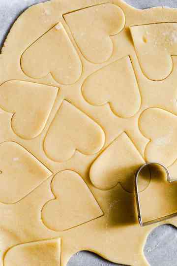 close up shot at cookie dough with heart shapes being cut out of it