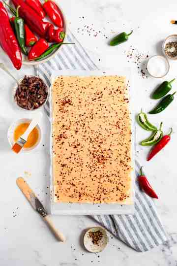 top view of puff pastry sheet with cream cheese and chilli flakes
