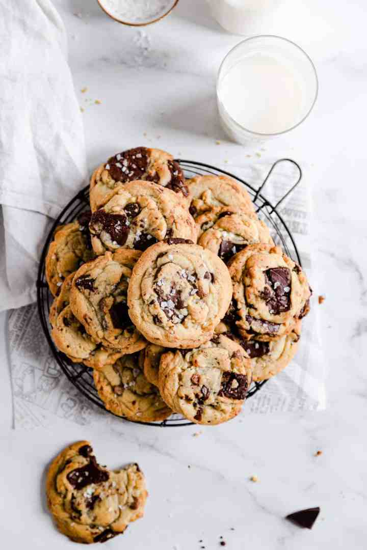overhead shot of chocolate chip cookies on a round wire rack with glass of milk