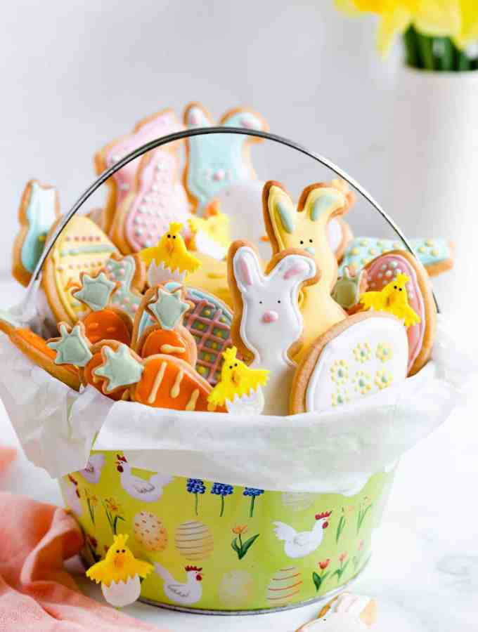 side close up of basket filled with Easter sugar cookies with coloured icing