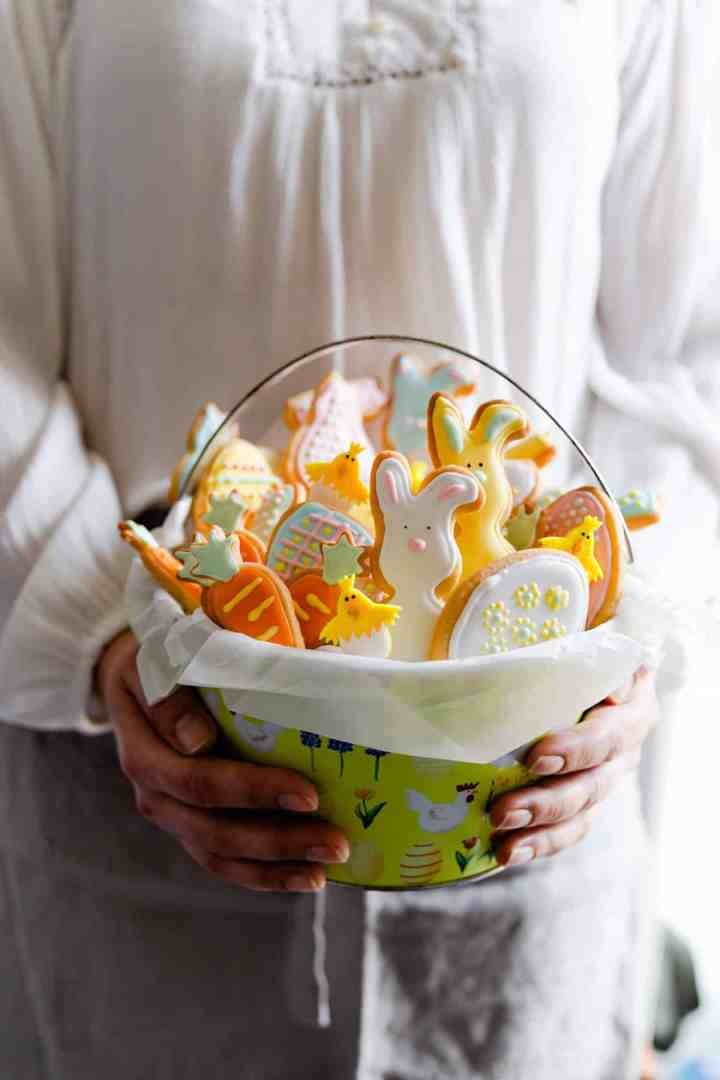 side close up of a person holding a basket filled with sugar cookies
