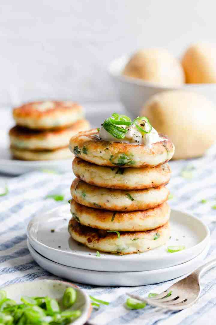 a side shot of stack of potato patties on a white plate
