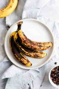 top view of 3 ripe bananas on a white plate