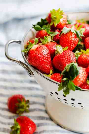 side close up at fresh strawberries in colander