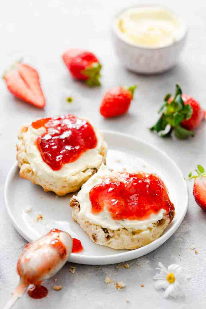 side close up at scone with strawberry jam and cream