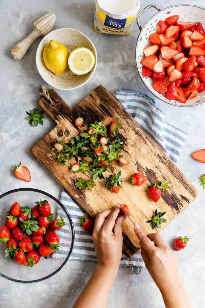 overhead shot of a person slicing strawberries on a chopping board