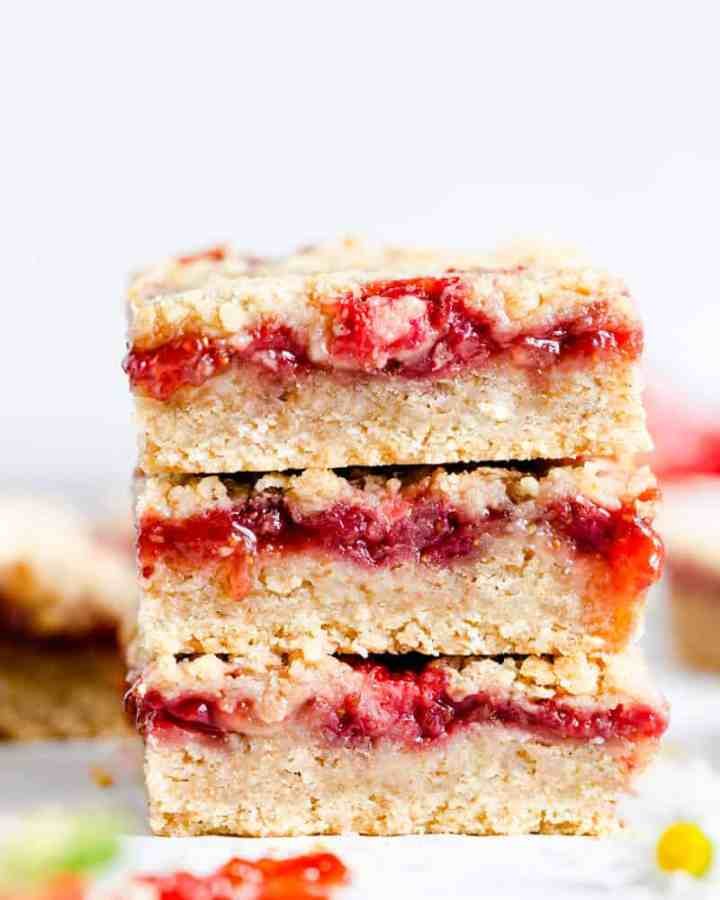 straight ahead angle super close up of 3 strawberry crumble bars stacked on top of one another
