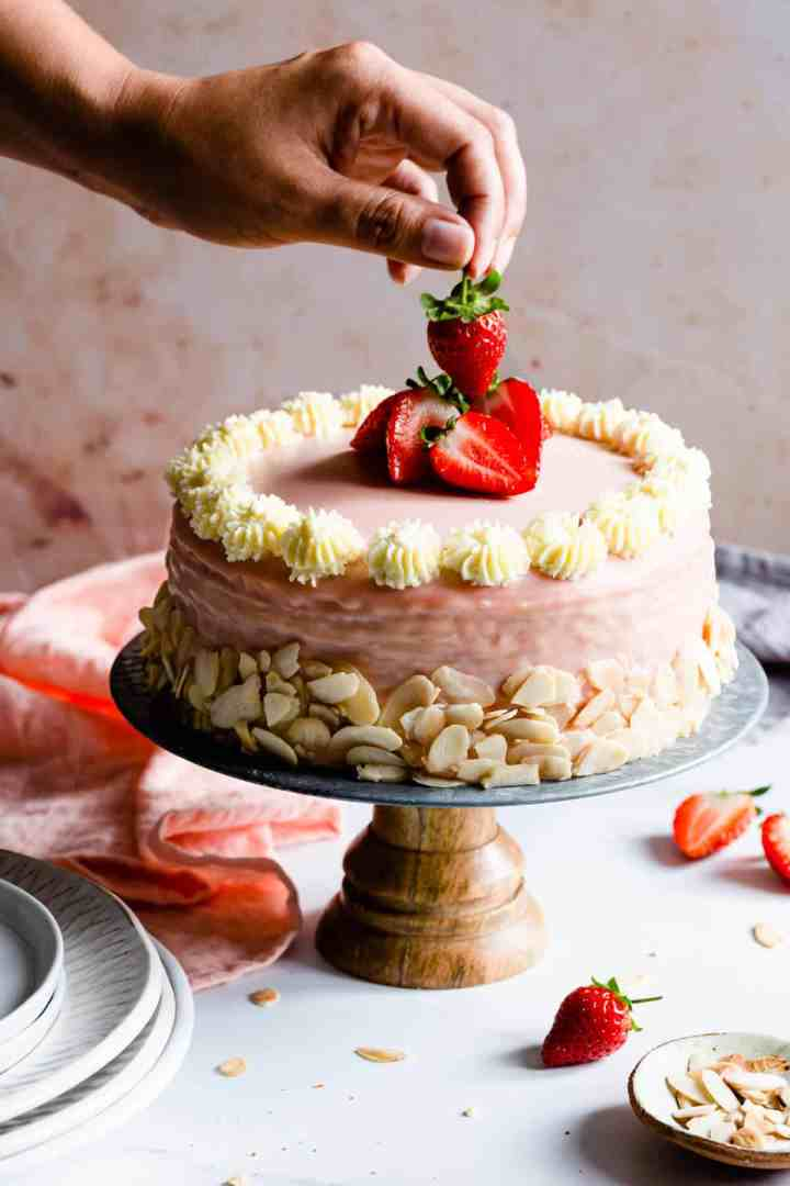 side shot of a hand lifting a strawberry from the top of the cake