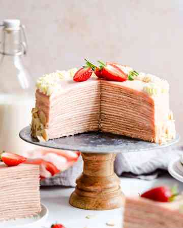 straight ahead shot of a strawberry crepe cake with couple of slices cut out revealing its inside