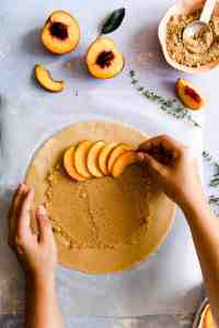 top view of sliced peaches being arranged onto galette dough