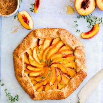 top view of baked peach galette with fresh thyme sprinkled on top