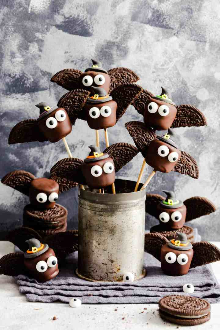 side shot of chocolate bats on bamboo skewers in a little cup