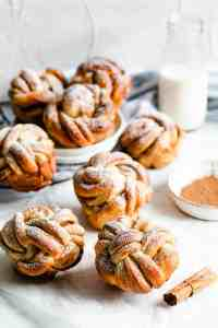 side angle shot of cinnamon buns with icing sugar and a bottle of milk in the background