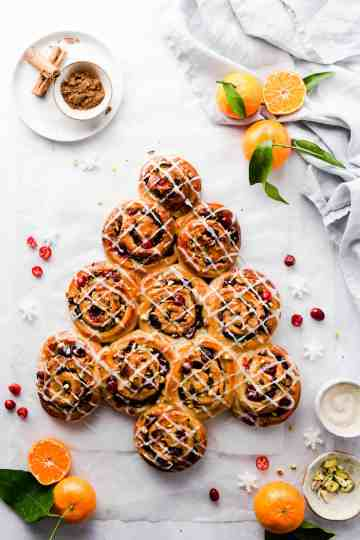 overhead shot of orange and cranberry Chelsea buns shaped into a Christmas tree