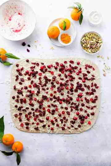 top view of a dough rectangle topped with marzipan and cranberries