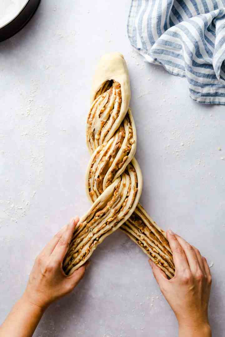 top view of a person twisting the dough for cinnamon and hazelnut bread
