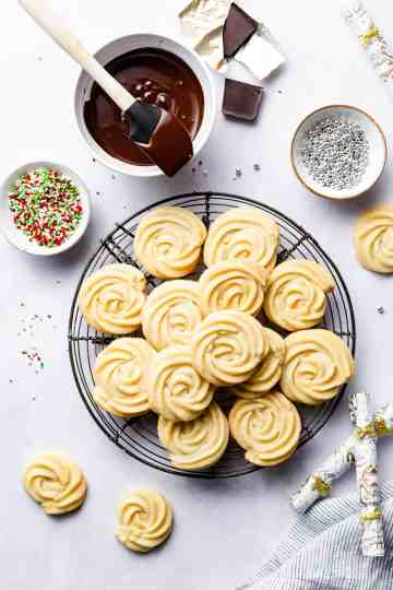 overhead shot of Danish butter cookies on a round cooling rack with sprinkles and melted chocolate next to it