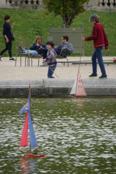 Kids playing with little sailboats at the Luxembourg Gardens in Paris