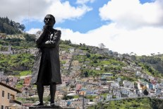 A statue in Quito with houses going up the hillside behind