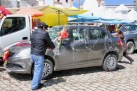 A family pouring beer on their car in preparation for having it blessed at the cathedral in Copacabana, Lake Titicaca, Bolivia