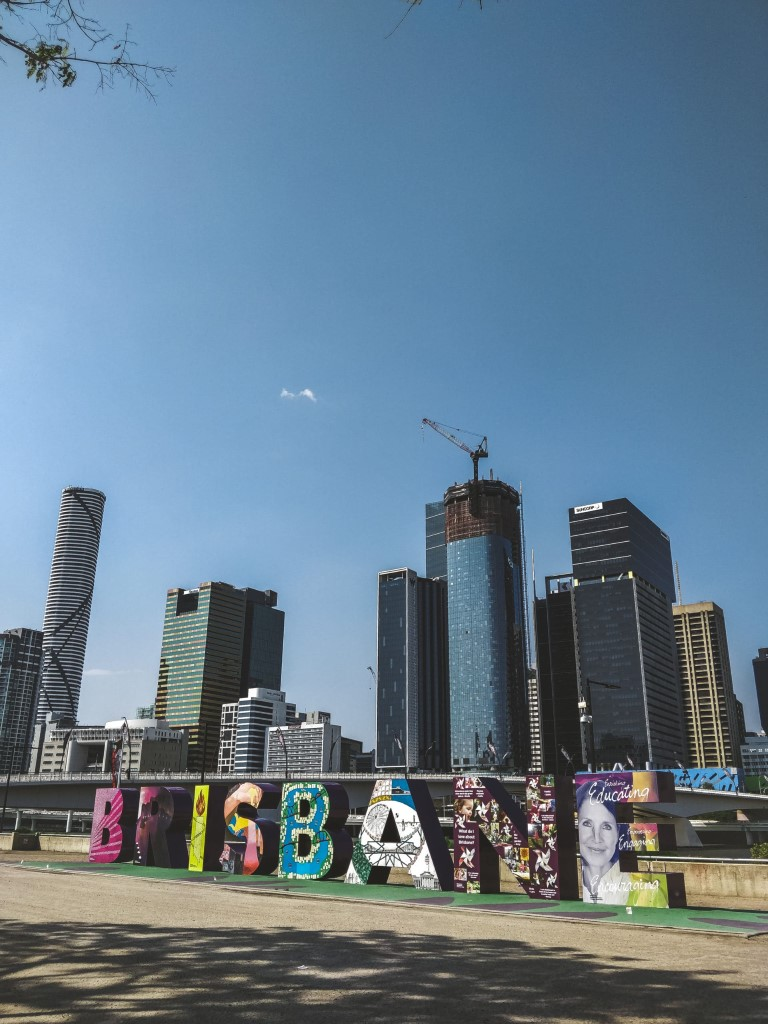 A colorful sign that makes up the word BRISBANE with towering buildings lined up at the back