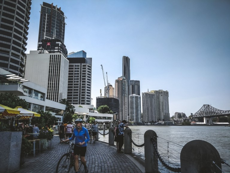 A river front surrounded by buildings with a man pushing his bike