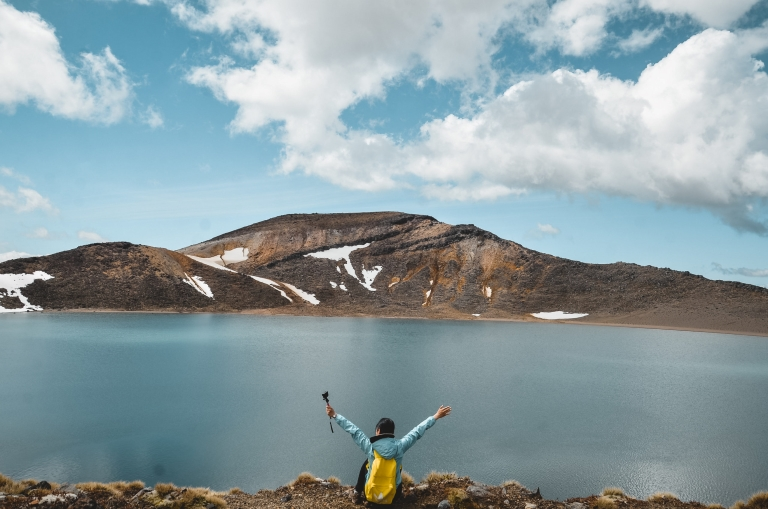 A girl with yellow backpack both hands raised on top looking at a blue lake